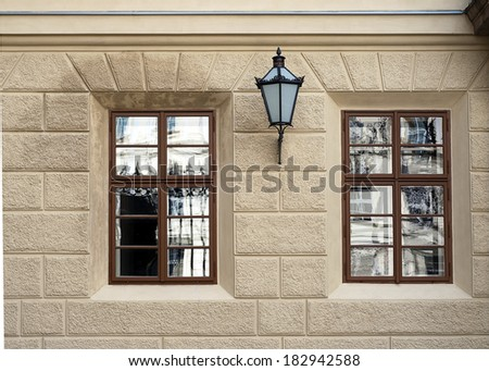 Two windows on an old stone house with an iron street lamp or lantern; Prague, Czech Republic. - stock photo