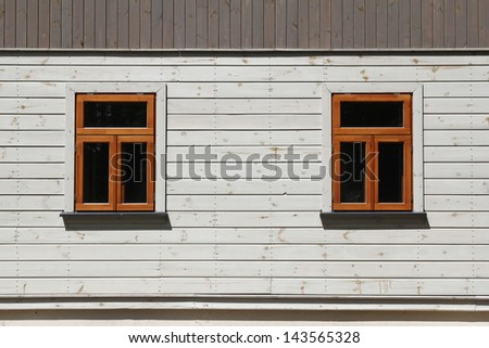 two windows on white wooden wall