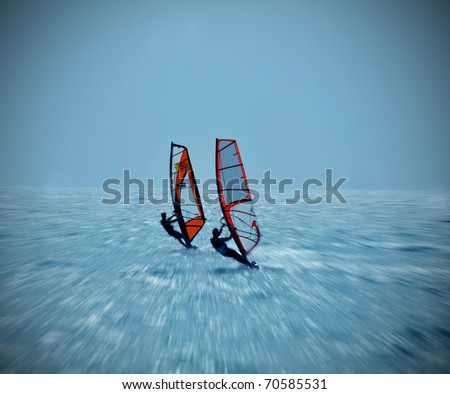 Two windsurfers in the ocean catching a wave - stock photo