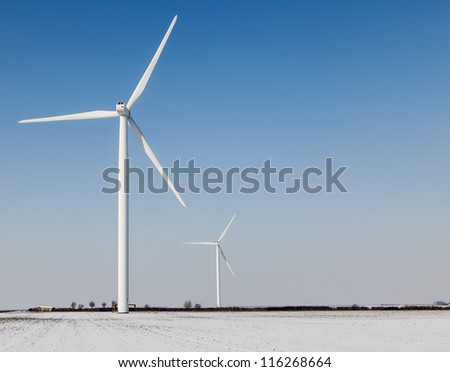 Two windturbines on a field covered by snow in winter. - stock photo