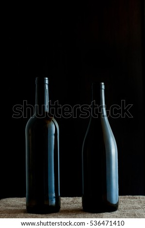 Two wine bottles on a linen tablecloth. Black background.