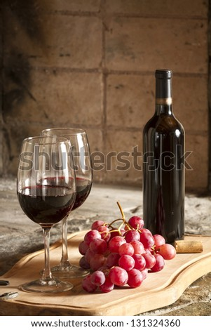 Two wine cups, grapes and a bottle of red wine - stock photo