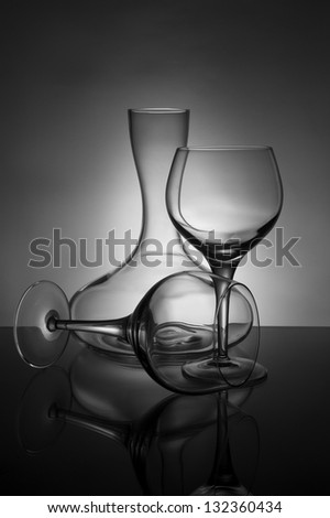 Two wine glasses and a decanter in black and white - stock photo