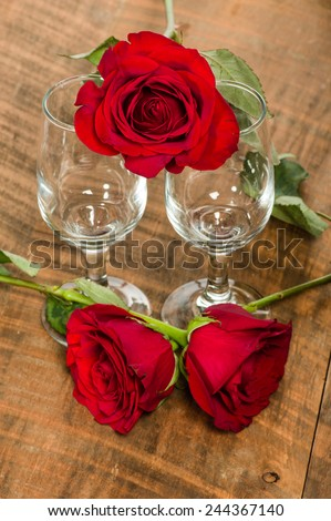 Two wine glasses and bright red roses - stock photo