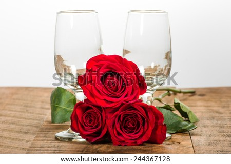 Two wine glasses and three red roses - stock photo
