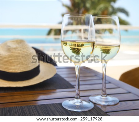 Two wine glasses at the table with white wine at sky and sea background - stock photo