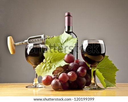 two wine glasses, bottle red wine with grape and leafs
