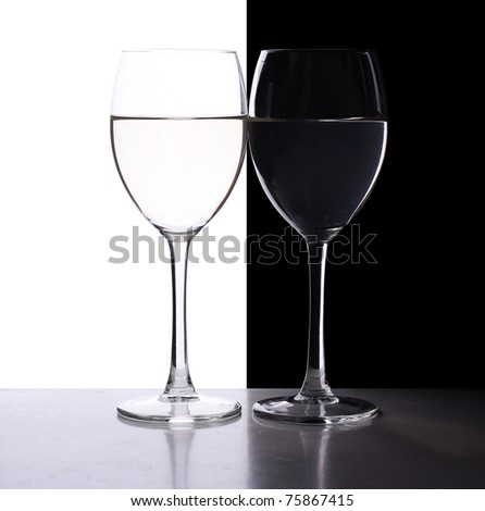 two wine glasses in backlight on the black and white contrast background