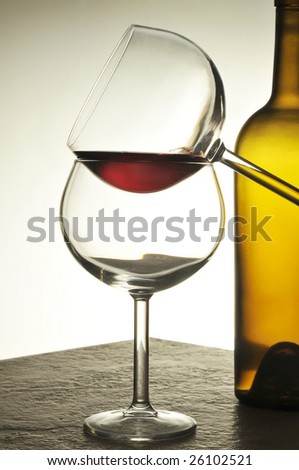 Two Wine Glasses in front of an empty bottle with warm tones and lighting