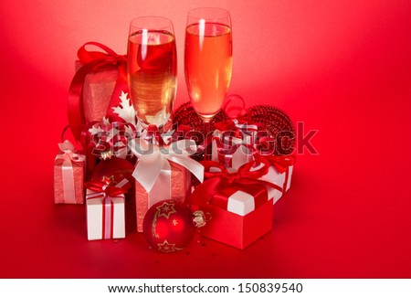 Two wine glasses with champagne, gift boxes with bows and tapes, Christmas spheres and serpentine on a red background