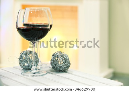 Two wine glasses with Christmas decor on fireplace background - stock photo