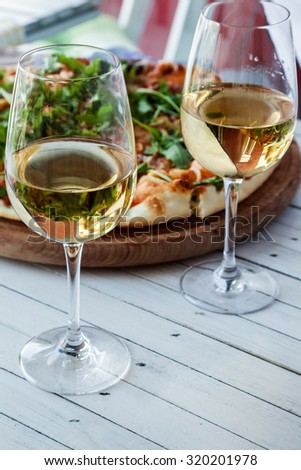 Two Wine Glasses With Delicious Pizza Behind