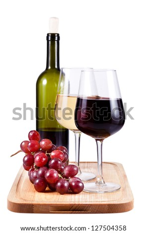 two wine glasses with red and white wine, bottle of wine and grapes on the carving board