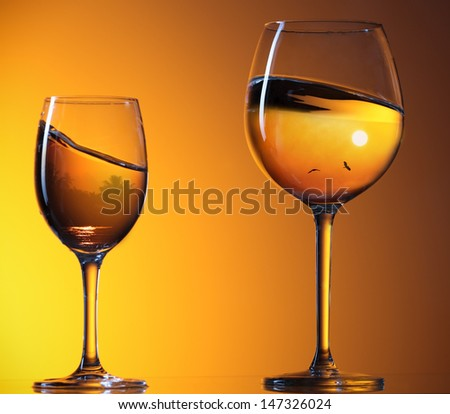 two wine glasses with reflections in the sunset - stock photo