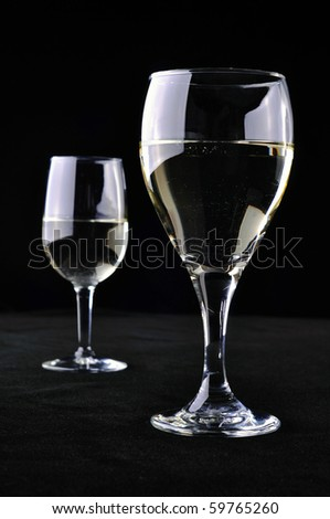 Two wine glasses with white wine, on a black background. - stock photo
