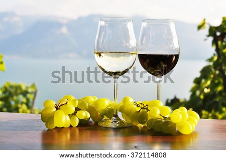 Two wineglasses and grapes against Geneva lake. Lavaux region, Switzerland. - stock photo