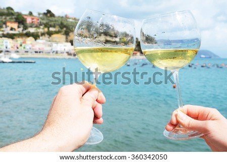 Two wineglasses in the hands against the harbour of Portvenere, Italy - stock photo