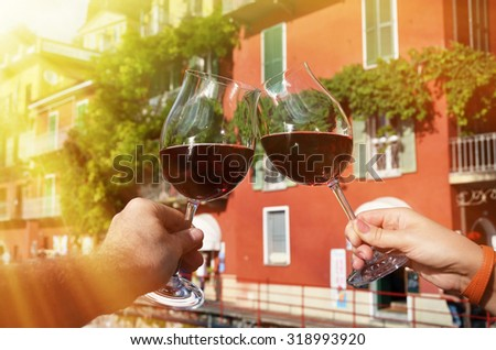 Two wineglasses in the hands. Varenna town at the lake Como, Italy - stock photo