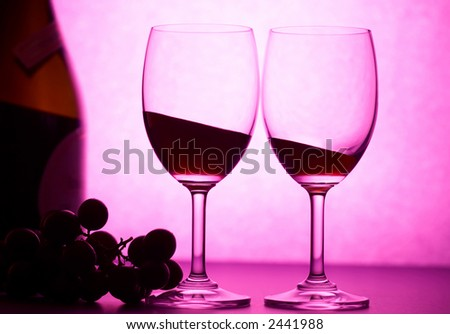 two wineglasses with some grape in pink light