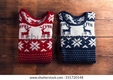 Two winter sweaters laid on a wooden table background - stock photo