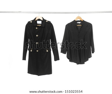 Two woman black clothes with coat on a hanger - stock photo