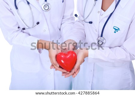 Two woman doctor holding a red heart - stock photo