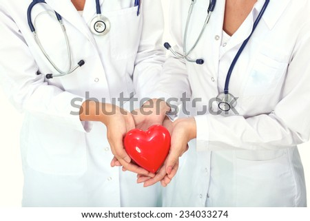 Two woman doctor holding a red heart, isolated on white - stock photo