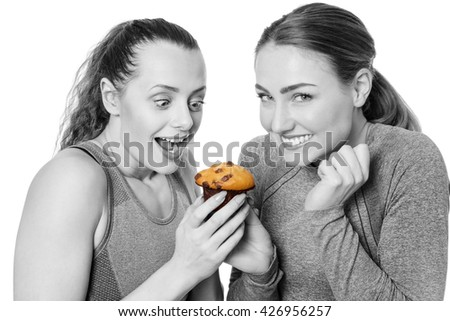 two woman dressed in fitness clothes getting excited about to eat a muffin