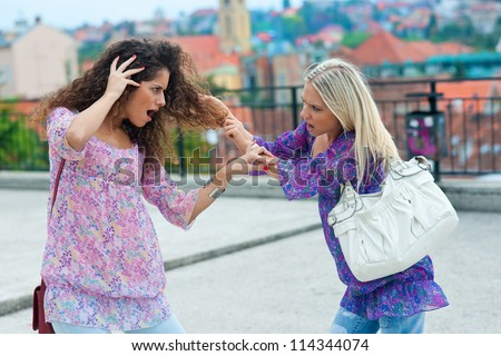 two woman fight each other in the street and pulling hair - stock photo
