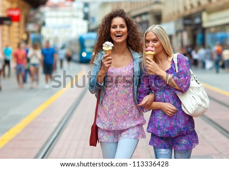 two woman friends walking on the street with ice cream and having fun - stock photo