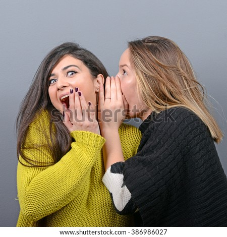 Two woman friends whispering secrets against gray background