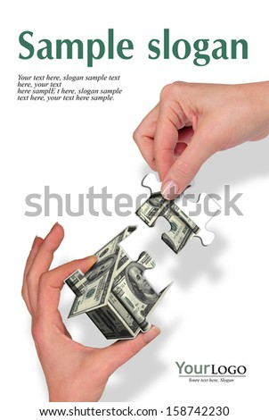 two woman hands holding a house of puzle pieces     - stock photo