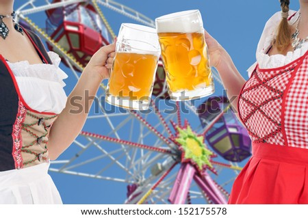 two woman in dirndl with beer mug and ferris wheel / Oktoberfest