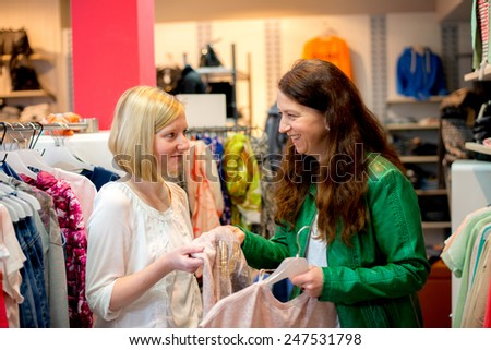two woman in the clothes shop looking for outfit