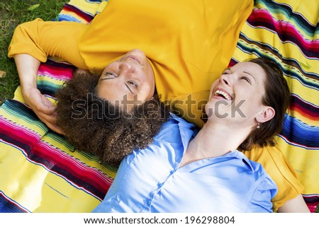 two woman lying on a blanket in a park and hugging each other - stock photo