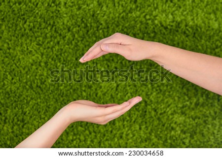 Two Woman's open hands making a protection gesture isolated on green background.