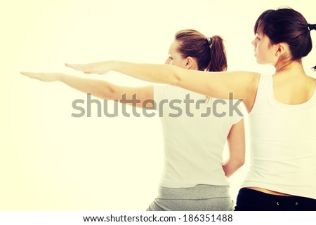 Two womans exercising, isolated on white background  - stock photo