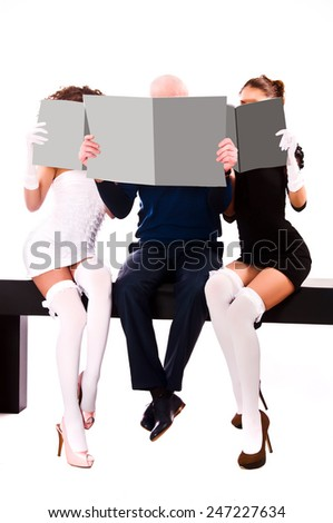 Two women and a man are holding gray magazines - stock photo