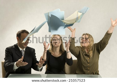 Two women and a man in a workplace setting.  They are smiling and have thrown some papers into the air. Horizontally framed shot.