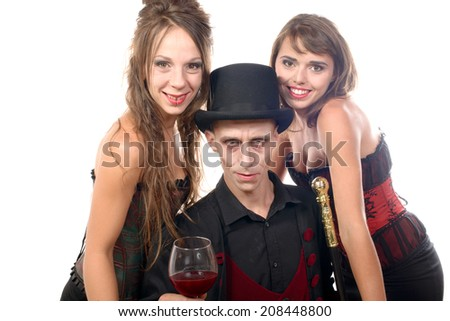 two women and a man in disguise halloween with glass of blood - stock photo