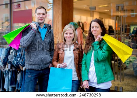 two women and a man in front of clothes shop