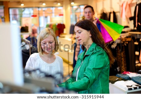 two women and a man in the clothes shop looking for outfit