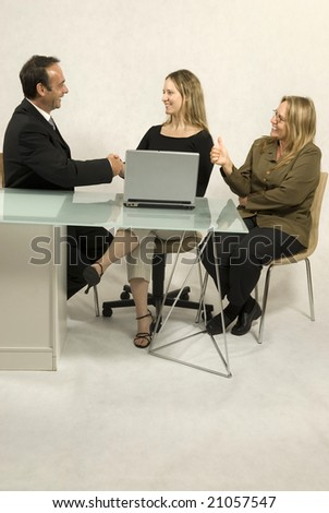 Two women and a man seated at a desk in front of a laptop, they are all smiling and the man and one woman are shaking hands.