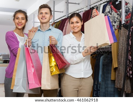 Two women and a man shopping in a boutique