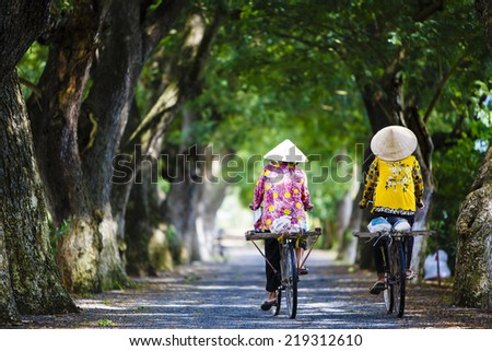 Two women and children are on the road by bicycle in the village at Chau Doc, An Giang Province - stock photo