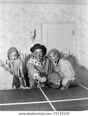 Two women and one man in a costume playing table tennis - stock photo