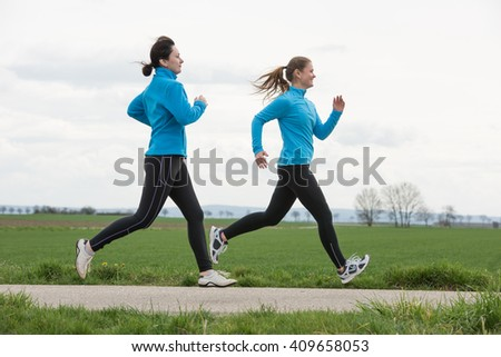 two women, 40 and 20 years old, jogging (running) outdoors