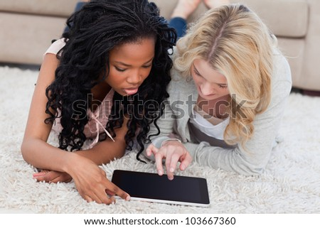 Two women are lying on the floor using a tablet - stock photo