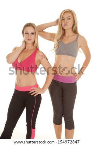 Two women are standing in their sports bras.