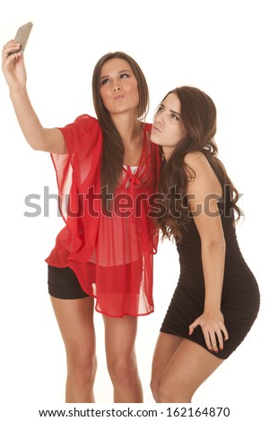Two women are taking pictures of themselves and making a kissy face. - stock photo